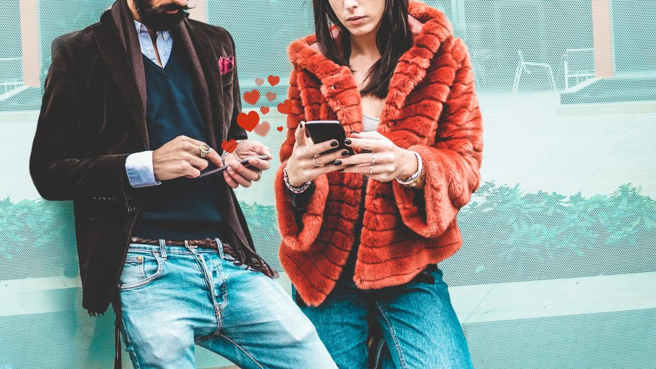 Trendy Influencers People Using Smartphone Social Media App Young Fashion Couple Watching Story Video On Mobile Cell Phone Technology Trends, Marketing And New Digital Job Concept Focus On Hands